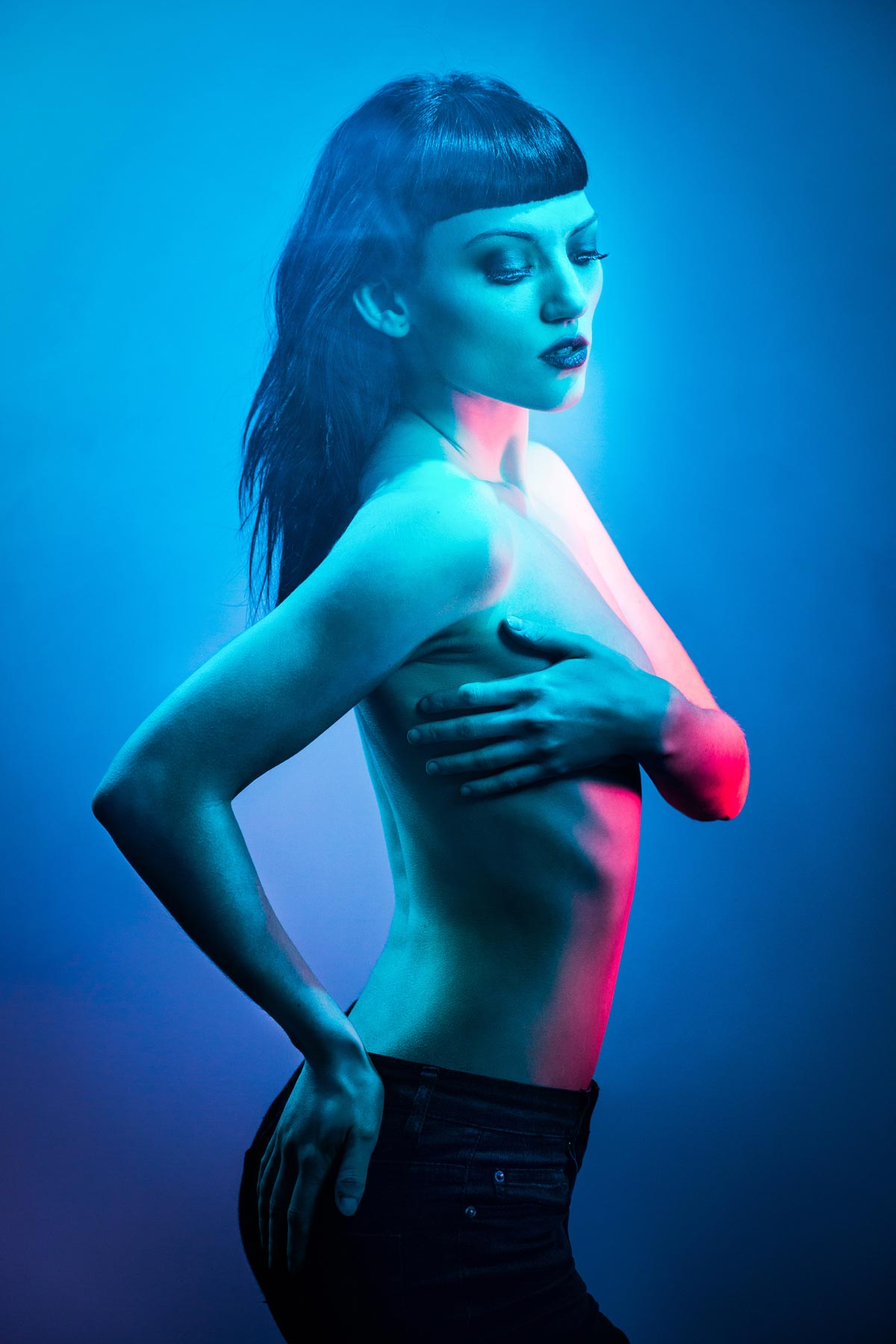A fashion shot using colourful gels of a girl with black hair lit in red and blue, naked top half covering her breasts, fashion photography by Nukemedia