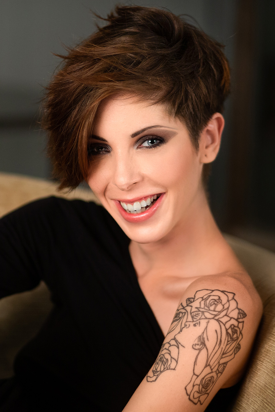 A photographic portrait of a beautiful girl with short brown hair and a tattoo on her arm, smiling at the camera, photography by Nukemedia