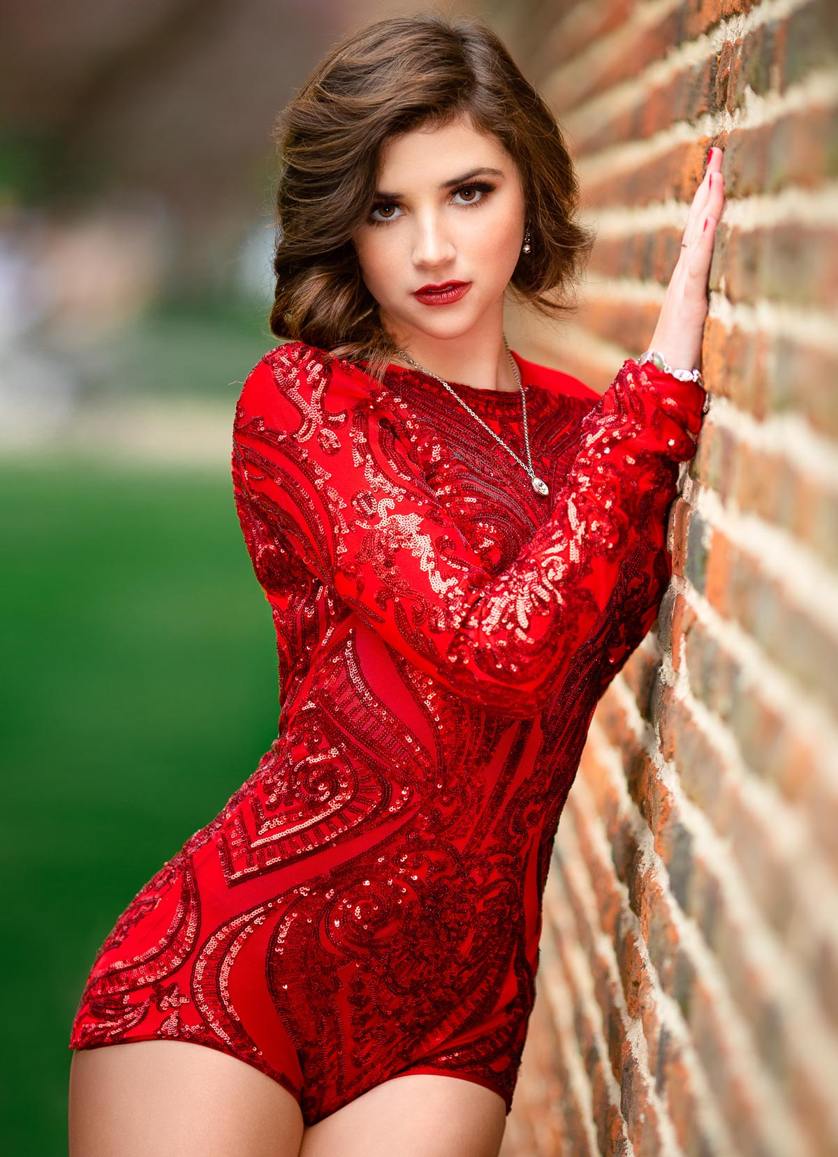 A beautiful young girl in a red sequin bodice leaning agains a brick wall, A blonde girl in a park full of roses in a red dress, photography by Nukemedia